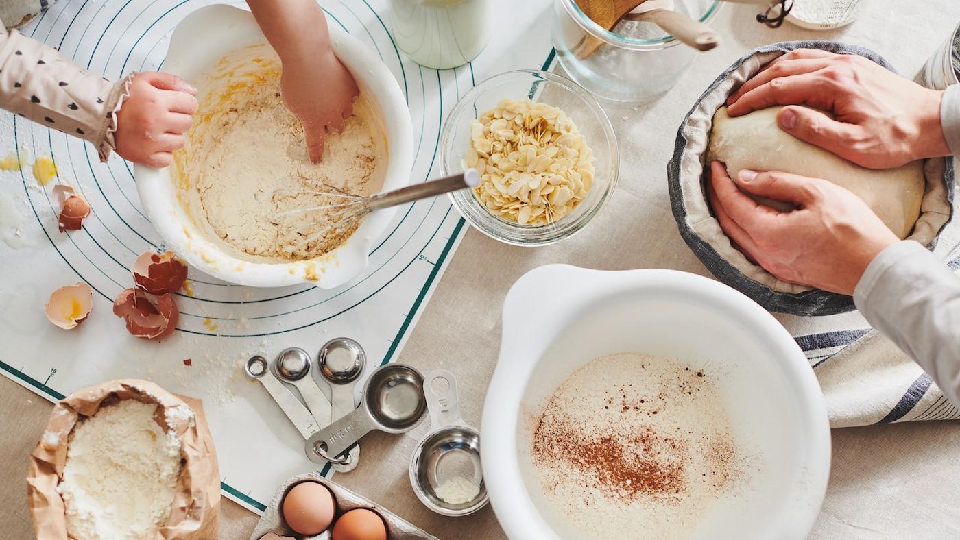 Une table en plein atelier de cuisson: œufs, farine et ustensiles. Les mains travaillent les pâtes dans des bols blancs VISPAD et dans un banneton.