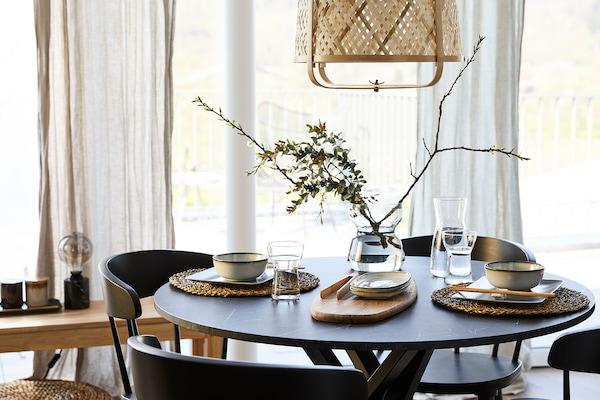 Une table est mise pour un repas, avec un vase au milieu de la table.