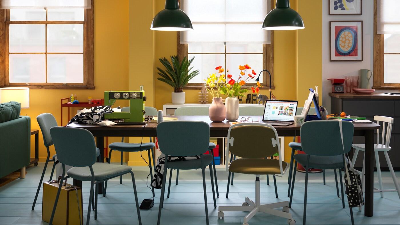 Une table extensible STRANDTORP brun foncé entourée de différentes chaises et divisée en différents postes de travail pour les activités de la journée.