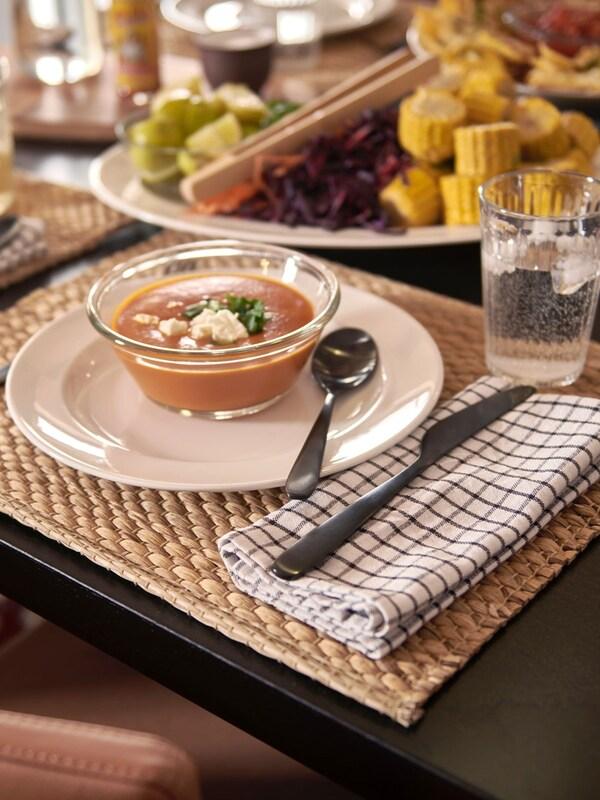Une table joliment préparée avec un bol de soupe qui repose sur un napperon UNDERLAG naturel.