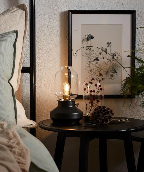 Une table KRAGSTA placée à côté du lit sur laquelle est posée une plante séchée sous une cloche en verre et une lampe LED dimmable TÄRNABY.