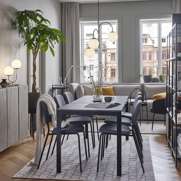 Une table noir/brun foncé et des chaises grises sur un tapis à motifs géométriques,  en dessous d'une suspension chromée à 3 bras.