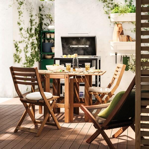 Une table pliable en acacia et des chaises à l'extérieur, avec un barbecue en arrière-plan.