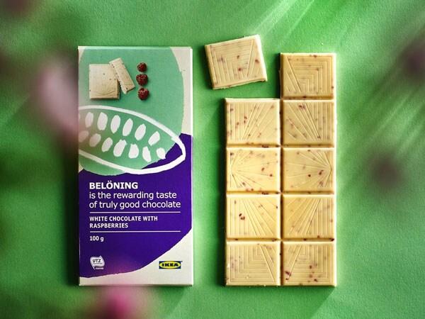 Une tablette de chocolat blanc BELÖNING aux framboises contre un arrière-plan vert.
