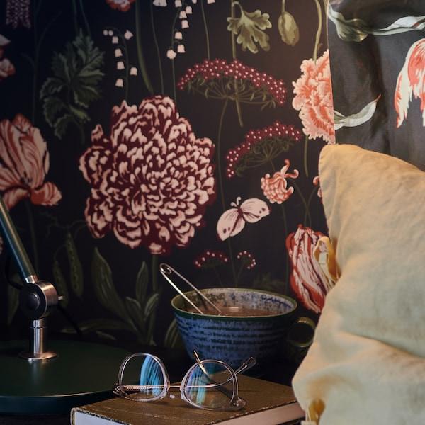 Une tasse et un livre sur lequel se trouve une paire de lunettes reposent sur une table de chevet, près d'un oreiller et devant un mur à motifs floraux.