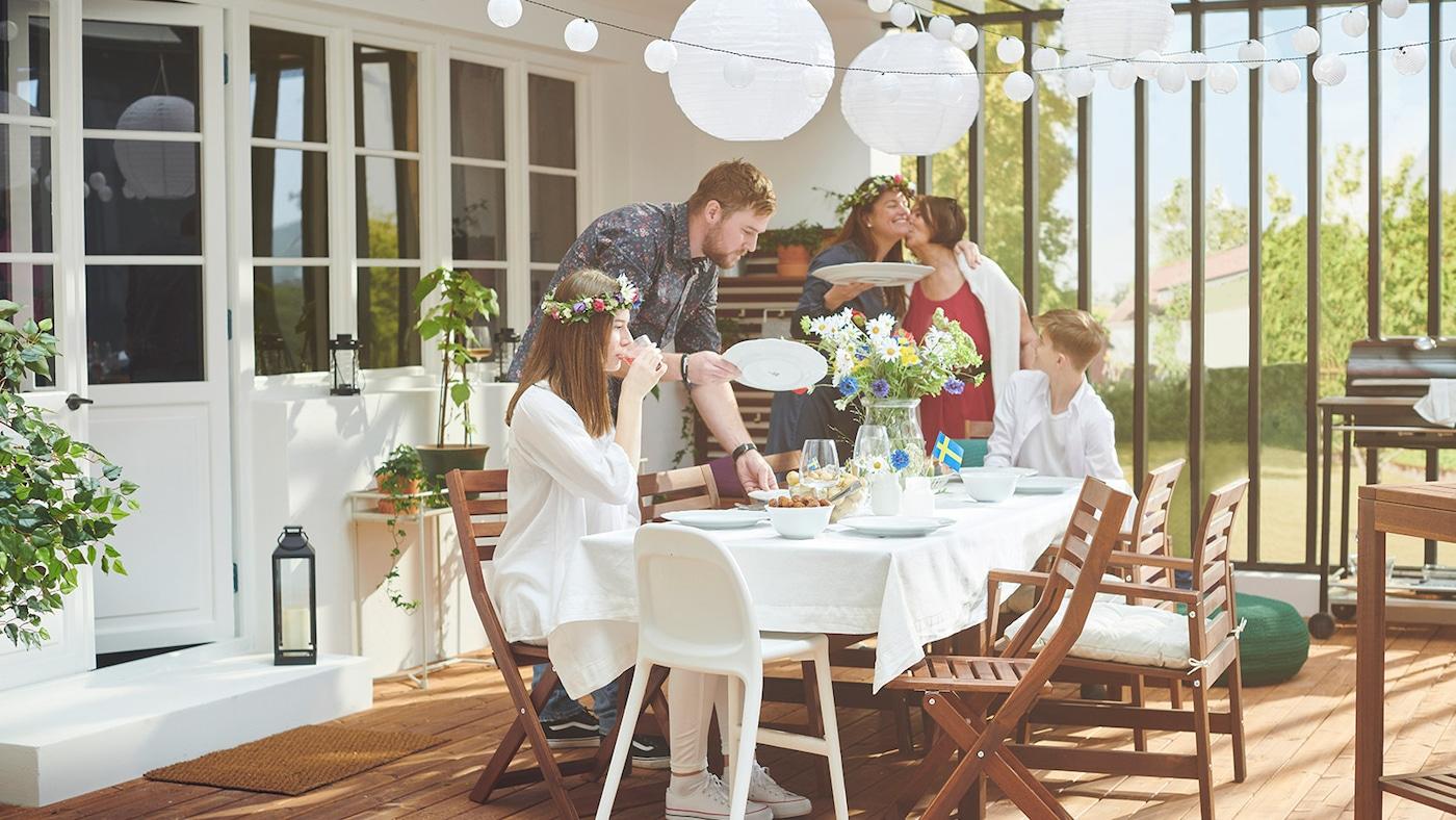 Une terrasse couverte ensoleillée avec des gens autour d'une table ornée de fleurs, de lanternes suspendues et d'un petit drapeau suédois.