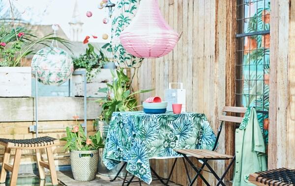 Une terrasse en ville avec une table de jardin recouverte d'un tissu à motif de feuilles, des chaises pliantes, des plantes en pots et des lanternes de couleurs.
