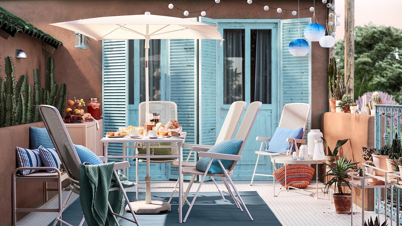 Une terrasse ensoleillée avec des murs en terre cuite, des portes bleues, une table blanche avec parasol, des chaises d'extérieur blanches et des coussins bleus.