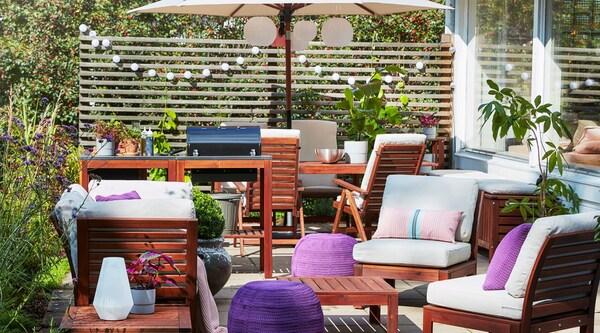 Une terrasse extérieure avec un ensemble de détente extérieur ÄPPLARÖ, des textiles beiges et roses, un repose-pieds violet et un plateau de boissons sur la table.
