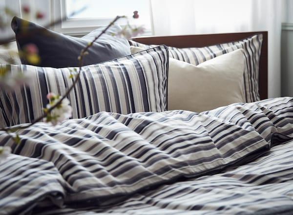 Une tête de lit avec du linge de lit en coton RANDGRÄS avec des oreillers et une housse de couette dans des tons de blanc et de gris, certains rayés.