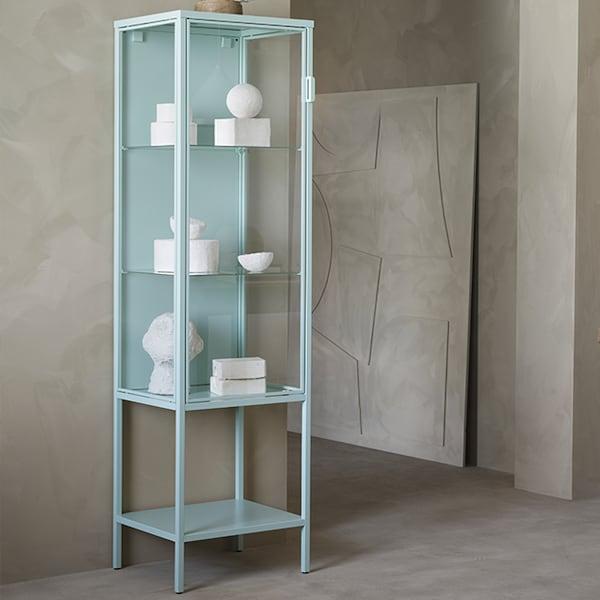 Une vitrine de rangement bleu clair contre un mur beige.