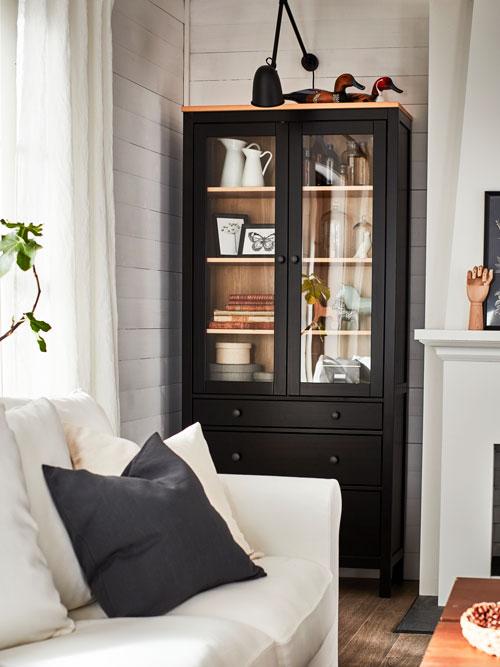 Une vitrine en pin massif à la finition noir-brun avec des bibelots, une applique noire au-dessus et un canapé blanc devant.