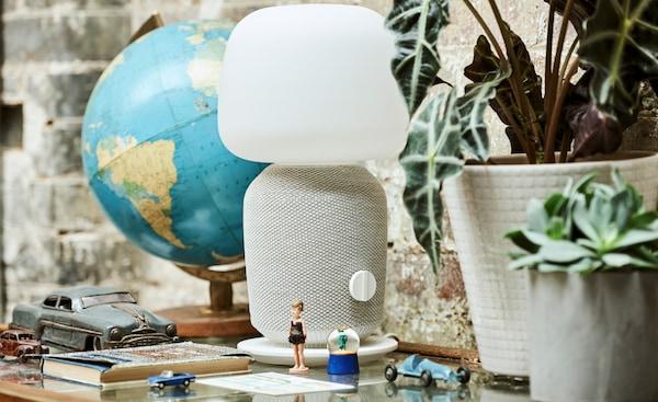 Une vitrine sur laquelle sont posés un globe terrestre, des plantes en pot, une lampe-cenceinte blanche, des figurines, des petites voitures, des boules à neige et un livre.