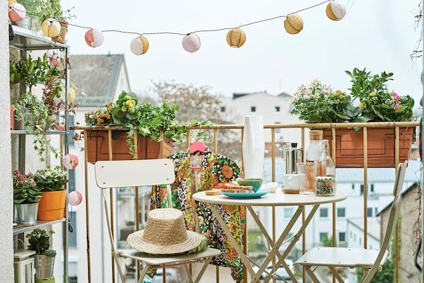 Une vue sur un balcon confortable rempli de plantes avec une table de terrasse et deux chaises.