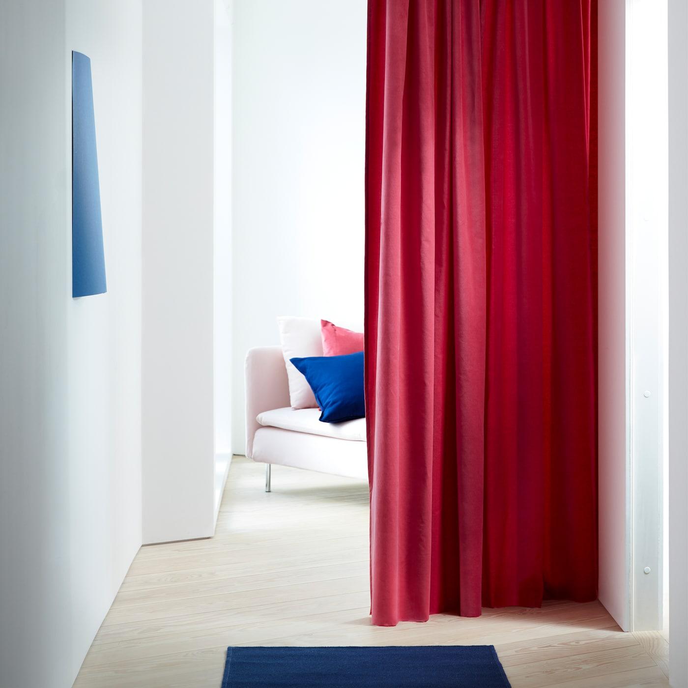 Unes cortines SANELA de vellut de cotó amb uns agradables tocs de vermell i marró clar que enfosqueixen l'habitació i que aquí es fan servir com a divisor d'una habitació.