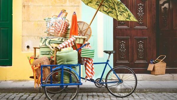 Unha bici azul, sobre unha aceira empedrada, ateigada de artigos de praia da colección IKEA SOLBLEKT.