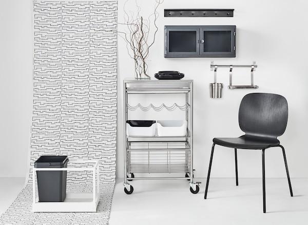 Unha cociña en branco e negro con guías de parede de aceiro inoxidable que liberan espazo de traballo e un caixón cun cubo do lixo.