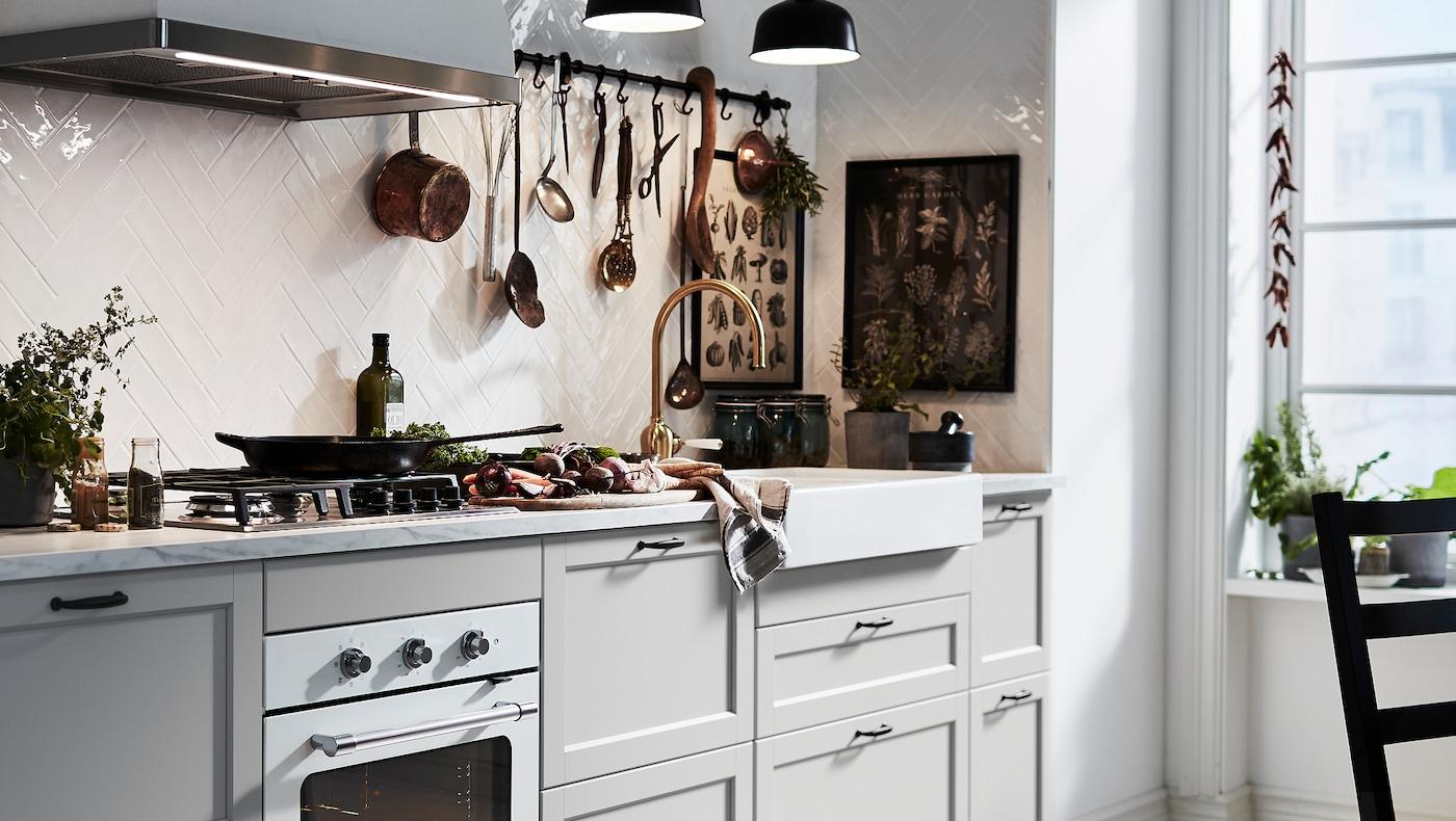 Unha cociña LERHYTTAN gris claro cun mesado de mármore branco e un vertedoiro branco con fronte vista.