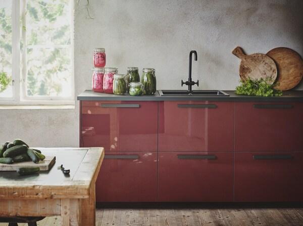 Unha cociña marrón avermellado escuro con acabado brillante con mesado, tiradores e vertedoiro en negro nunha estancia con paredes grises texturizadas.