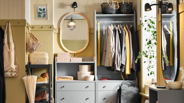Unha cómoda de caixóns HAUGA e un armario aberto HAUGA con roupa, caixas e cestos nun pequeno recibidor.