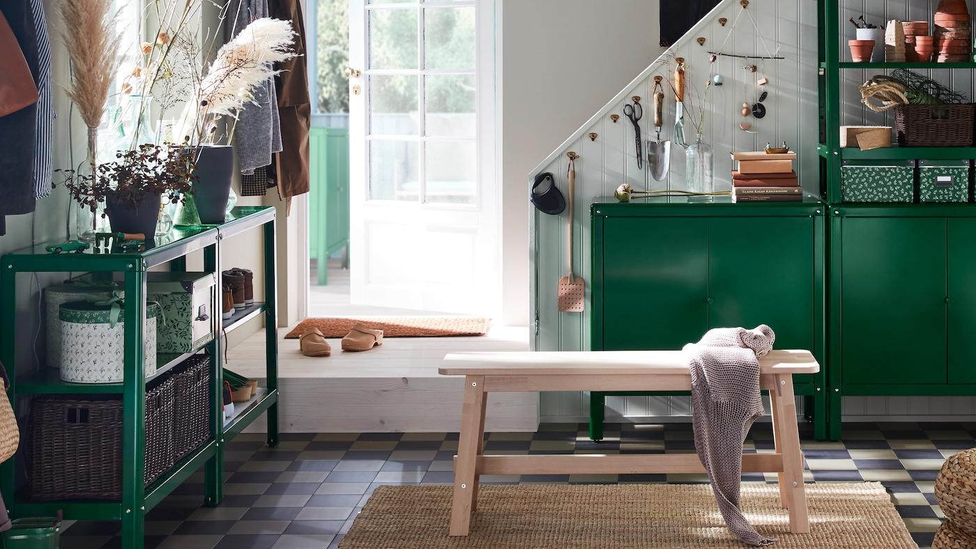 Unha entrada cun banco NORRÅKER e estantes e armarios KOLBJÖRN nos que se gardan caixas, obxectos domésticos e plantas.