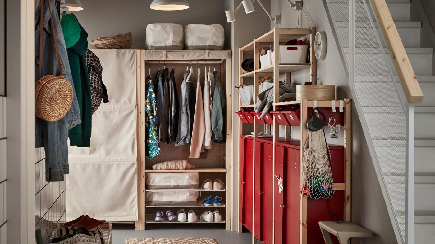 Unha entrada cun estante e almacenamento IVAR que inclúe armarios e caixóns vermellos; hai roupa, zapatos e artigos domésticos gardados.