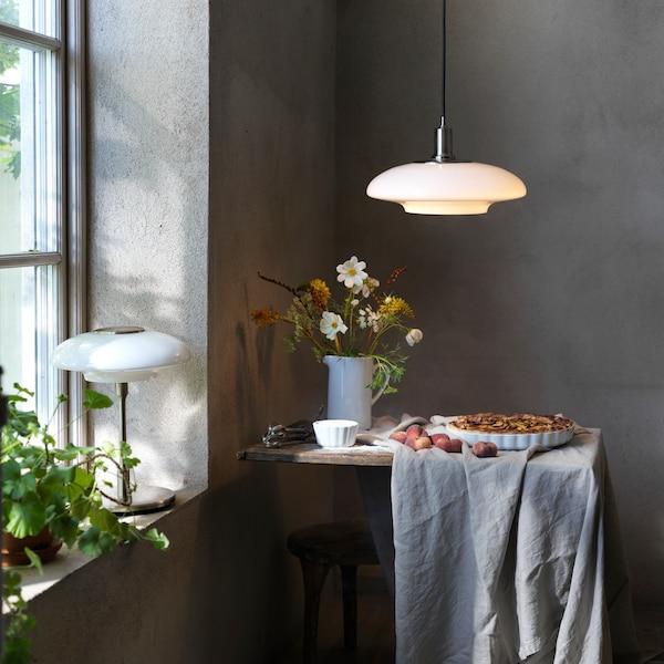 Unha lámpada de mesa TÄLLBYN sobre un peitoril e outra de teito sobre unha mesa cunha torta e flores.