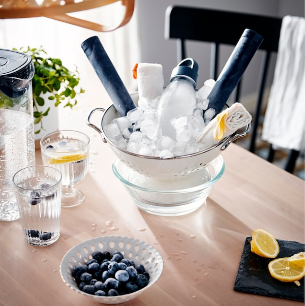 Unha mesa con distintos sistemas para arrefriar, como unha xerra e uns vasos de auga conxelada e un coadoiro cheo de xeo enriba dun recipiente.
