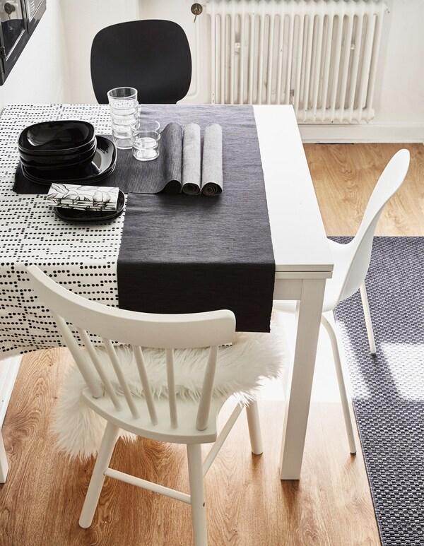 Unha mesa de cociña branca renovada combinando distintos estilos de cadeiras brancas e un mantel de puntos.