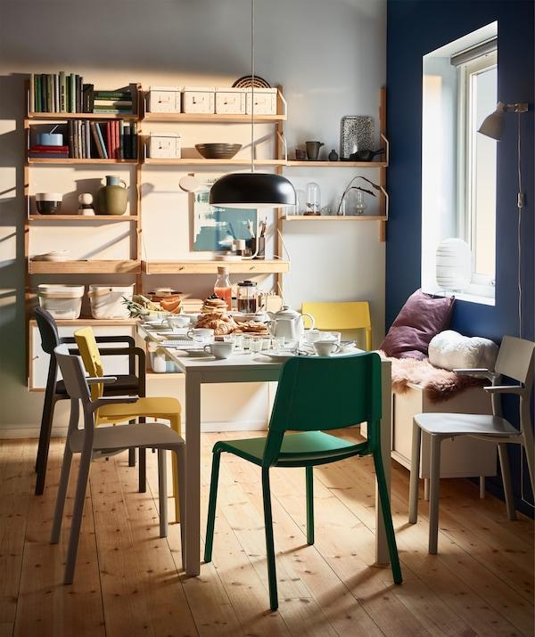 Unha mesa de comedor co almorzo posto, rodeada por coloridas cadeiras amontoables JANINGE.