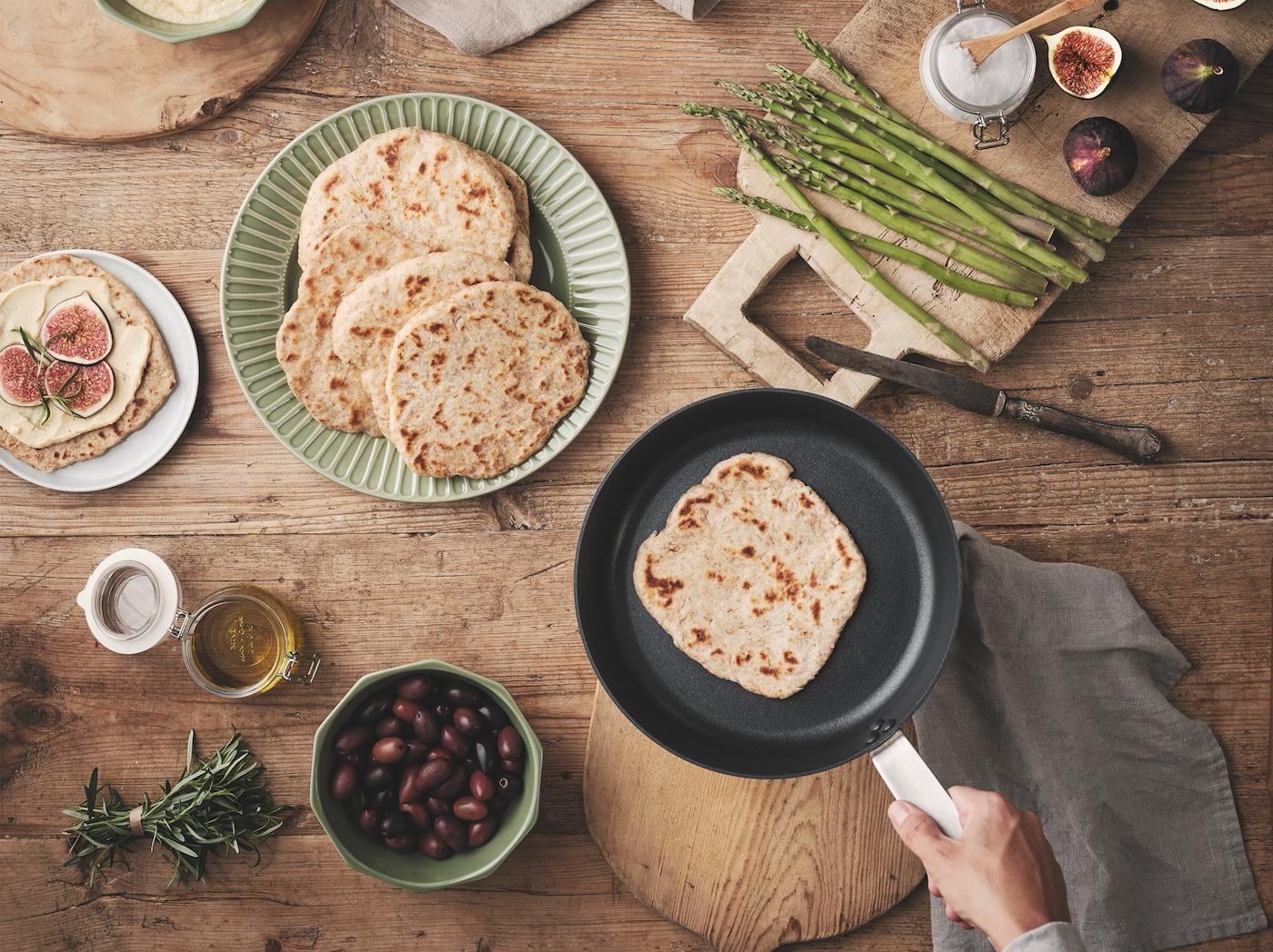 Unha mesa de madeira con tortas de pan KNÅDA sobre un prato verde e unha tixola, e varios condimentos ao redor, como espárragos e olivas.