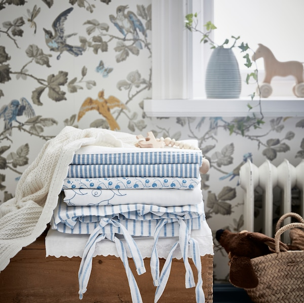 Unha morea de téxtiles enriba dunha caixa de madeira nun cuarto infantil cunha funda nórdica e unha funda de almofada GULSPARV, xunto con cortinas GULSPARV.