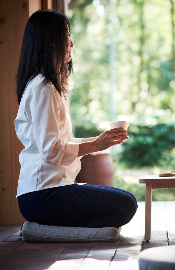 Unha muller senta no chan, nun coxín para cadeira OMTÄNKSAM, e suxeita unha cunca coas mans.