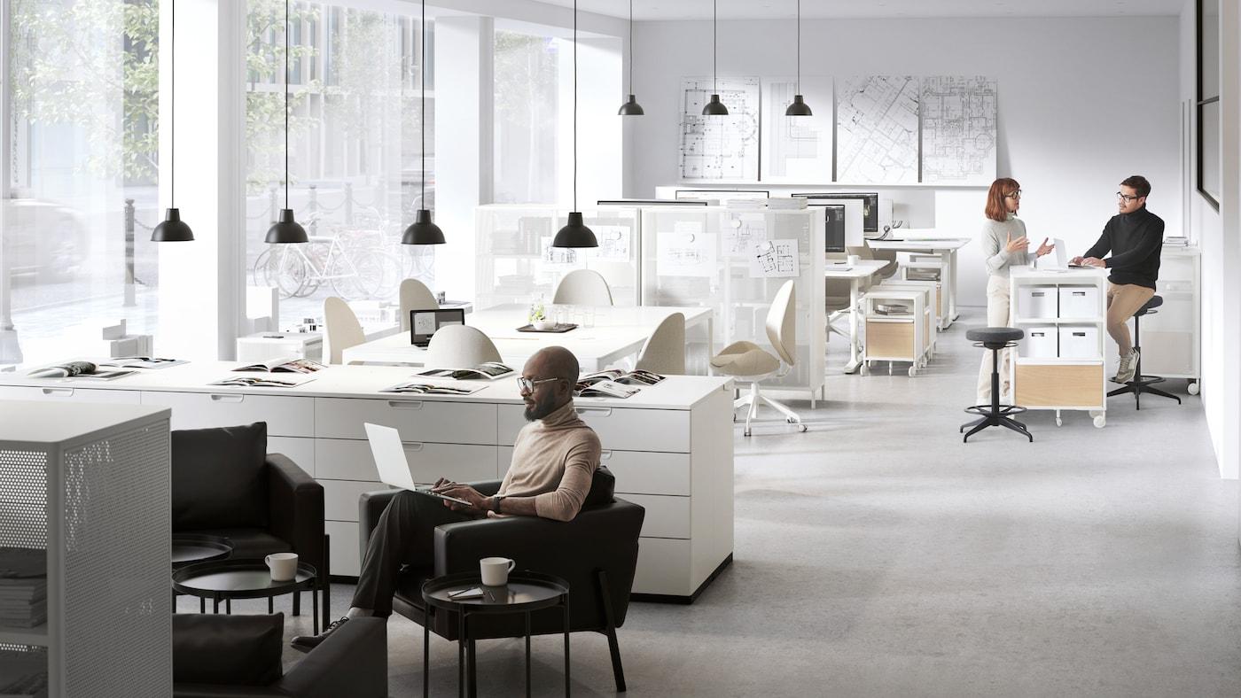 Unha oficina aberta con dúas zonas para desconectar. Un home traballa nunha cadeira de brazos KOARP e dúas persoas conversan xunto a un estante.