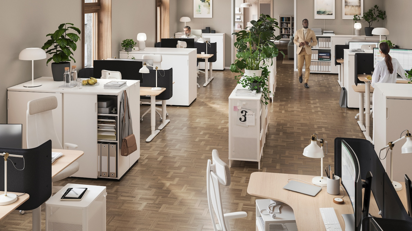 Unha oficina aberta cun estante central decorado con plantas, e estacións de traballo con iluminación nas esquinas.