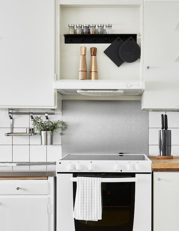 Unha vista da vitrocerámica da cociña cunha guía colgante para secar os pratos e gardar os utensilios para liberar espazo de mesado.