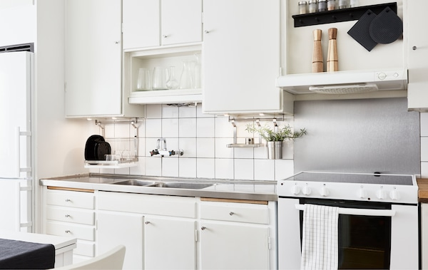 Unha vista dunha cociña branca con armarios, cociña, vertedoiro de aceiro inoxidable e andeis para gardar os utensilios de cociña.