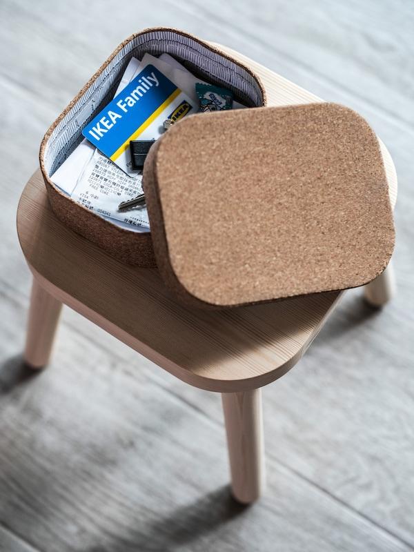 Uno sgabello su cui è appoggiata una scatola che contiene documenti e una carta IKEA Family.