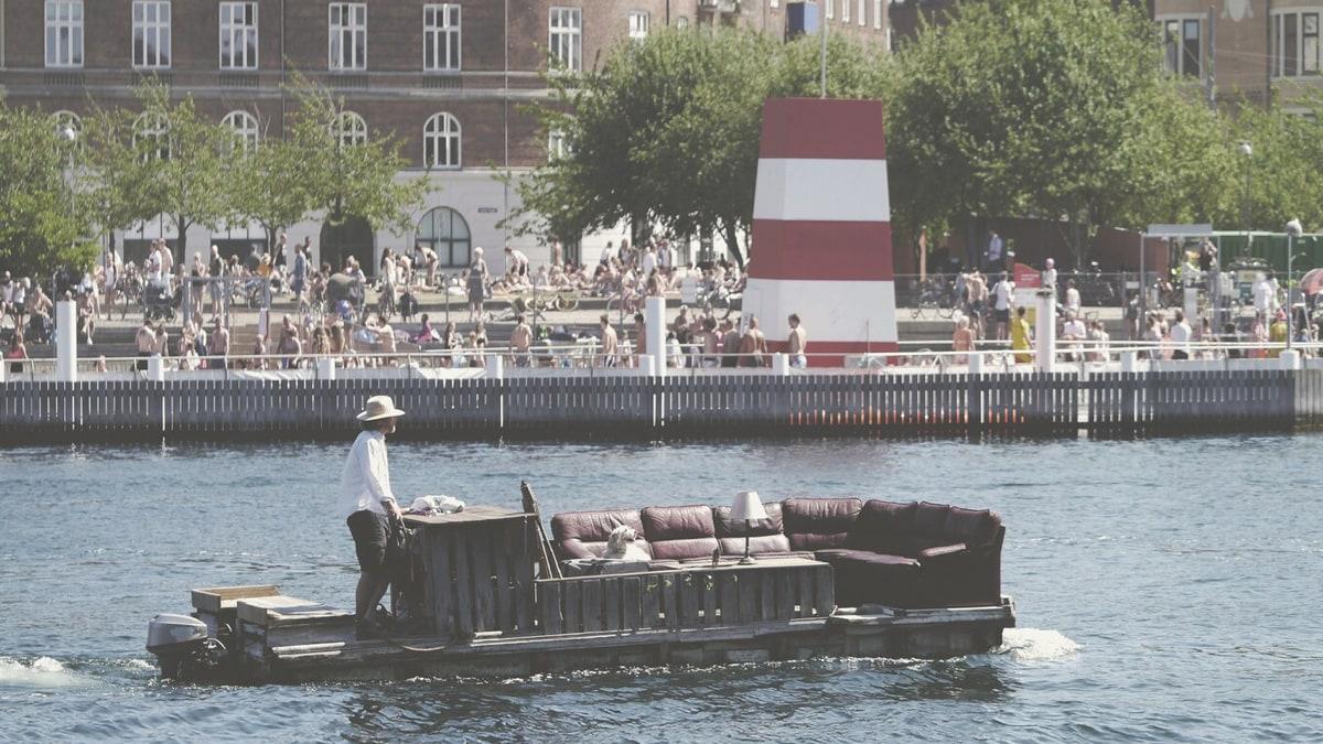 Uno spazio pubblico in riva al fiume con palazzi e alberi, persone che socializzano, e un uomo che guida una barca con sopra un divano - IKEA