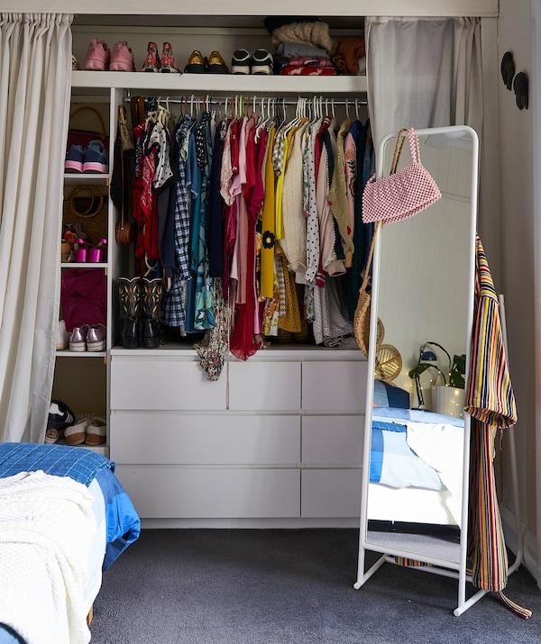 Uno specchio da terra e, dietro le tende, due cassettiere, ripiani e bastoni appendiabiti - IKEA