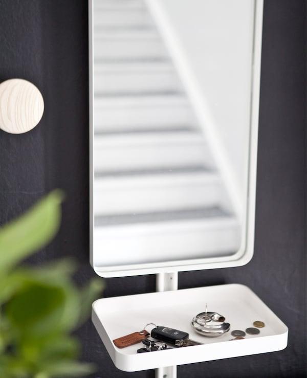 Uno specchio e un vassoio contenente chiavi e monetine sullo sfondo di una parete nera - IKEA