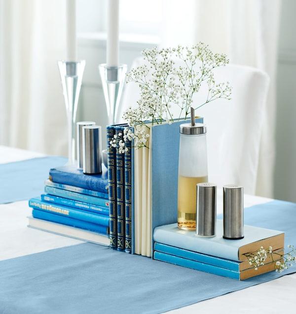 Unos libros azules con velas, flores velo de novia, aceite y saleros y pimenteros a modo de centro de mesa.