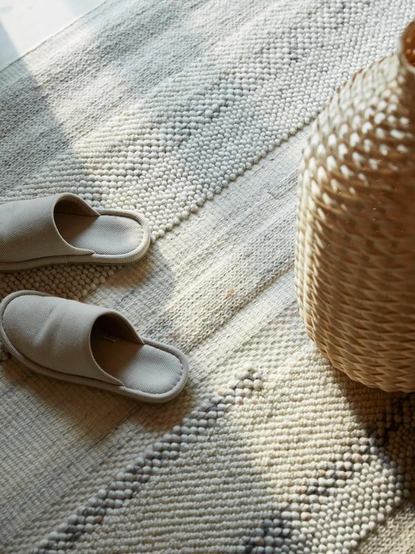 Uns chinelos bege e uma jarra em bambu entrelaçado em cima de um tapete BRÖNDEN tecido à mão.