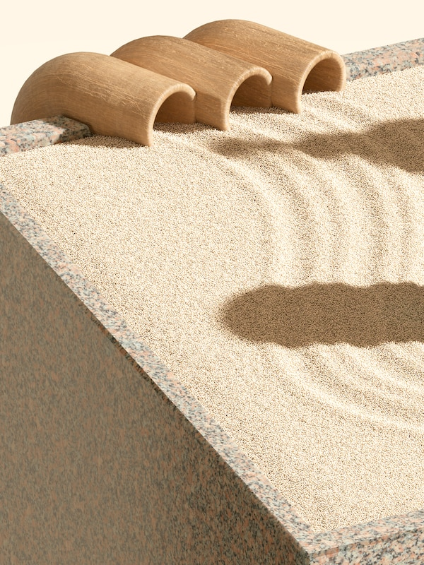 Uns sendeiros curvos saen de tres tubos de madeira no bordo dunha caixa de granito chea de area amarela.