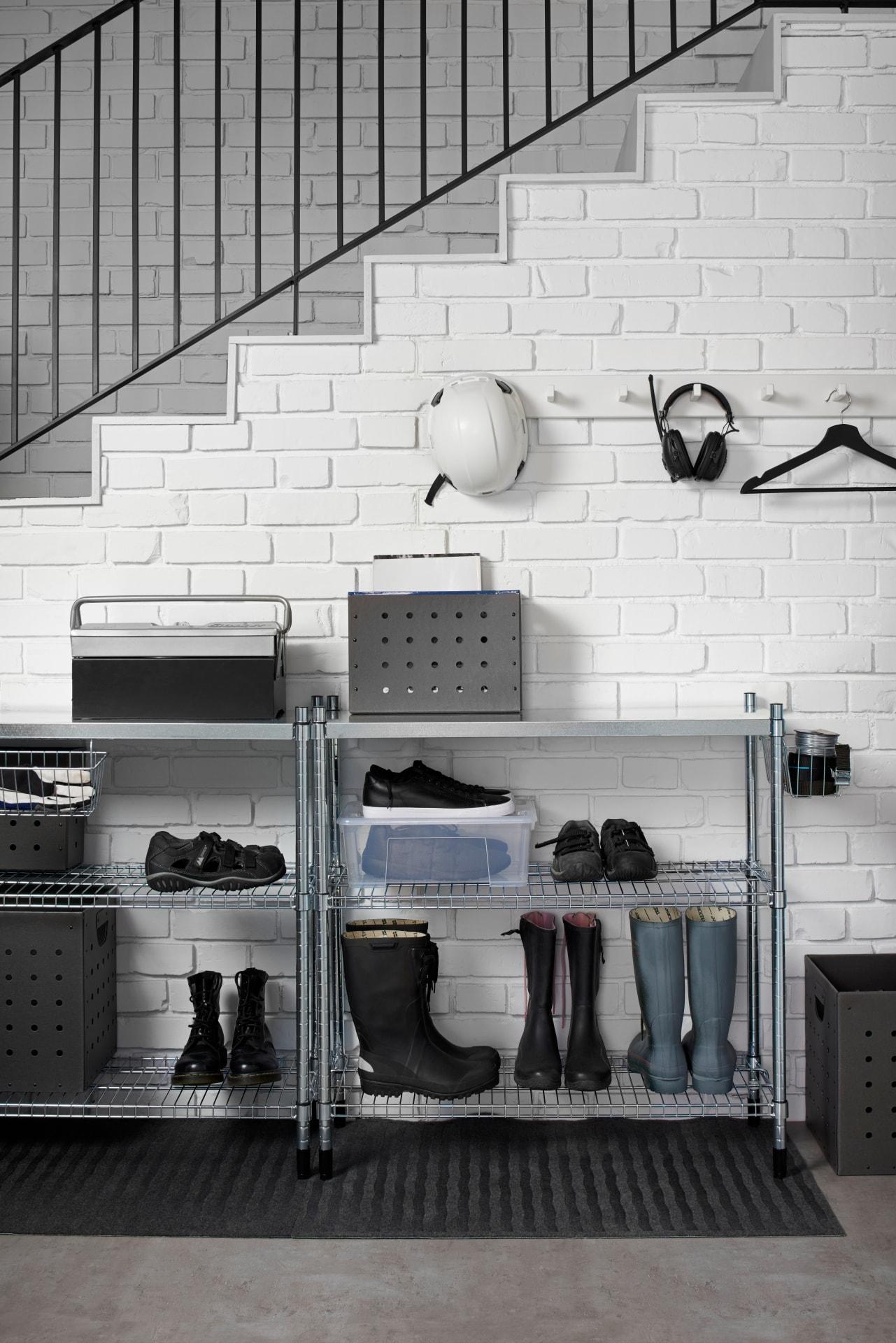 Unter einer weißen Steintreppe steht ein graues Regal mit Schuhen, Boxen & einer weißen Garderobe mit Helm.
