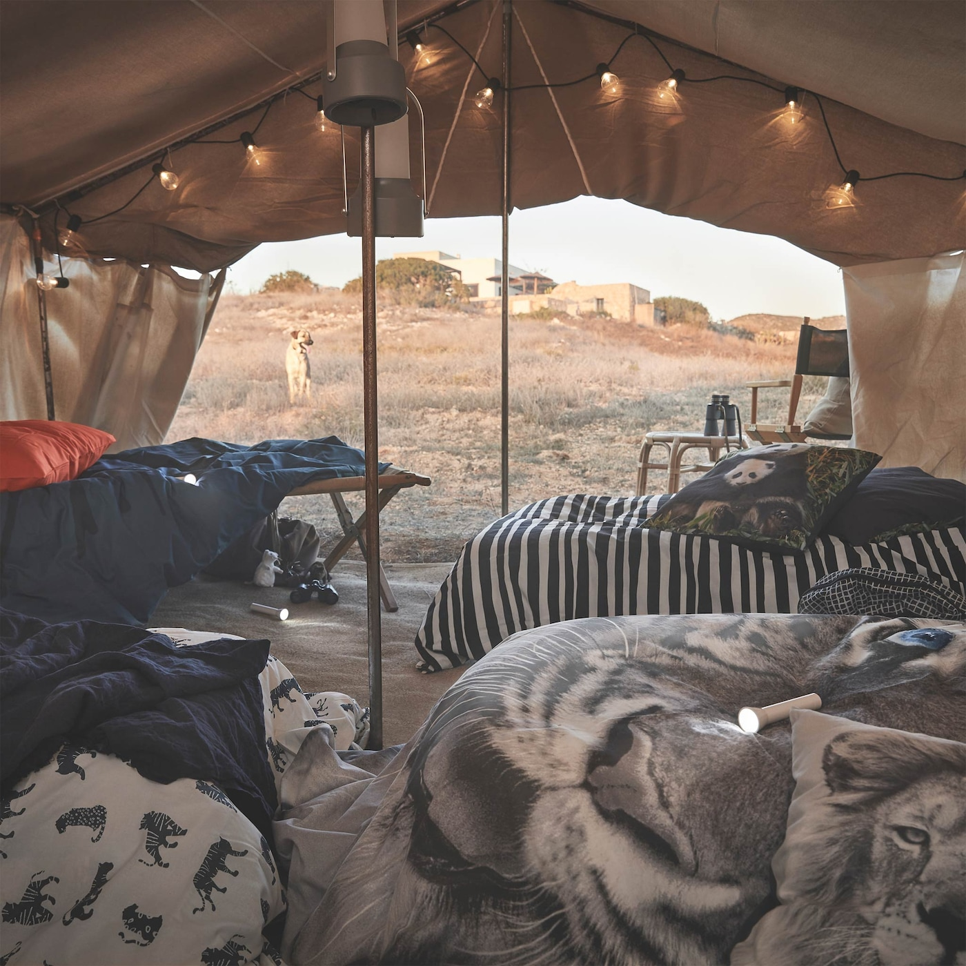 URSKOG dekbedovertrekken, hier getoond op bedden in een tent, zijn gemaakt van duurzamer katoen en zijn versierd met op wilde dieren geïnspireerde prints.