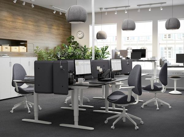 Urządzona na czarno i szaro przestrzeń biurowa z ustawionymi naprzeciw siebie i tworzącymi boksy czarnobrązowymi biurkami BEKANT z regulacją wysokości.