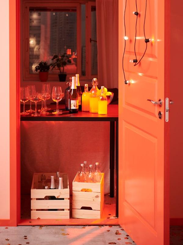 Ușă larg deschisă și decorată prin care se vede o masă cu băuturi în interiorul camerei. Alte sticle în lădițe KNAGGLIG sub masă.