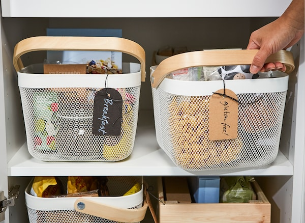 Use IKEA RISATORP white steel mesh storage baskets to arrange food by mealtime or by allergy. The mesh ventilates food to stay fresh longer, and is easy to grab by its wooden handle.