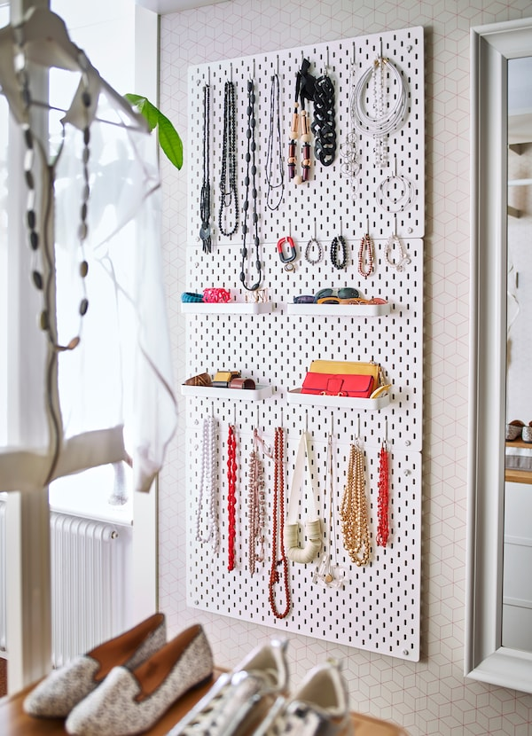 Use multiple IKEA SKÅDIS white pegboards to hang your jewelry and accessories, using add-on white shelves, hooks, pegs and elastic coords.